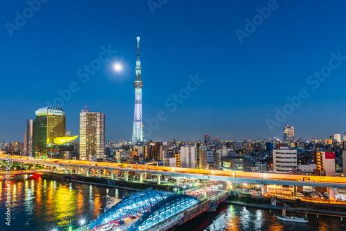 Photo Tokyo Skytree and Sumida river at night with full moon in Asakusa district, Tokyo city, Japan