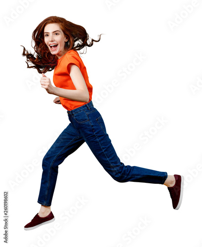 Full length happy ginger woman in shirt and jeans jumping. Wall mural