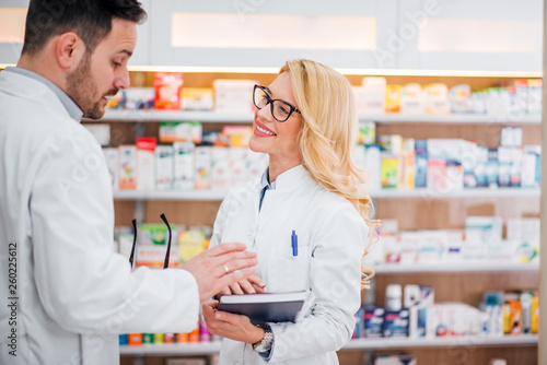 Fotografie, Obraz  Male pharmacist explaining rules to his new female colleague.