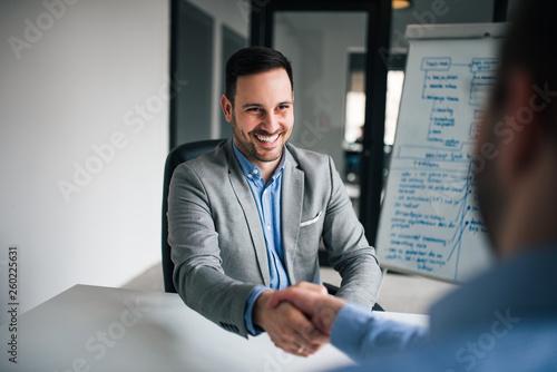 Valokuva  Smiling businessmen handshaking over the office desk after effective negotiation