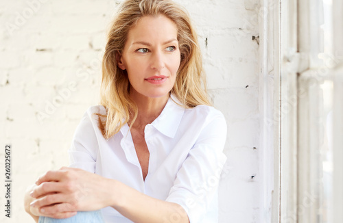 Photographie  Attractive mature woman portrait while relaxing at the window