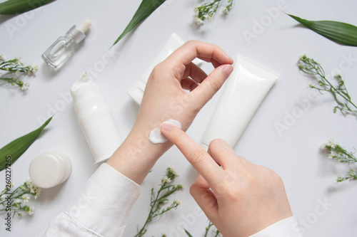 Obraz Scientist/Pharmacist applying moisturizer lotion on her hand for efficacy testing of natural organic skincare products in laboratory. Beauty cosmetic research and development concept. Top view. - fototapety do salonu
