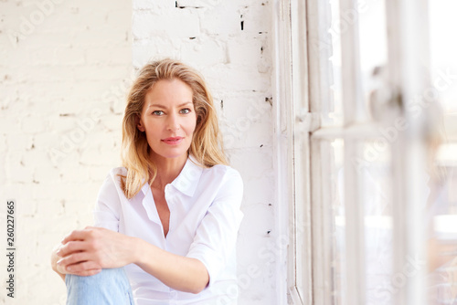 Fototapeta Attractive mature woman portrait while relaxing at the window obraz