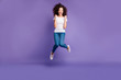 Full length body size photo yelling beautiful she her lady fists cheerleader jump high discount sale shopping wear casual jeans denim white t-shirt sneakers isolated purple violet bright background