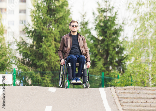 A young man in a wheelchair rides along the park road. Tapéta, Fotótapéta