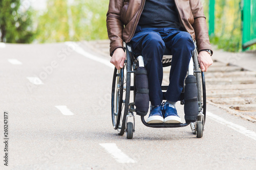 Foto A young man in a wheelchair rides along the park road.