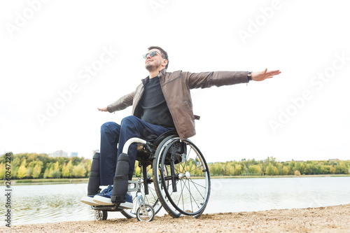 Valokuva  Young man sitting in a wheelchair by the lake.