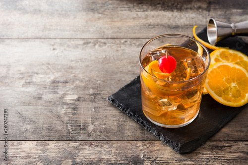 Obraz Old fashioned cocktail with orange and cherry on wooden table. Copyspace - fototapety do salonu