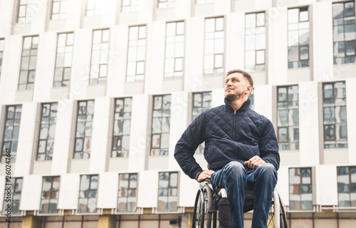 Valokuva  Young man in a wheelchair against the backdrop of a modern high-rise building