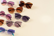 Different Sunglasses On Yellow Background. Summer Banner. Copy Space. Optic Shop