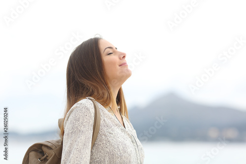 Fotografia  Happy woman on the beach breathing fresh air