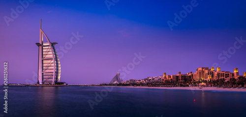 Photo  The illuminated Burj al Arab at dawn with the coastline of Dubai