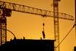 working shot with the silhouette of building houses and cranes