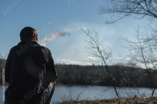 Foto op Aluminium Fantasie Landschap A lonely man sits on the Bank of the river in the cold early morning and smokes