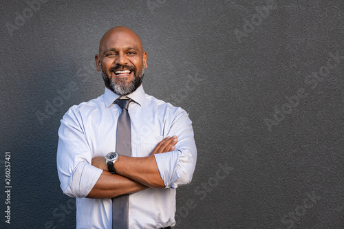 Fotografia  Happy mature businessman standing with folded arms