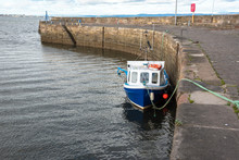 View Of A Small Fishing Boat Tied Up To A Quay
