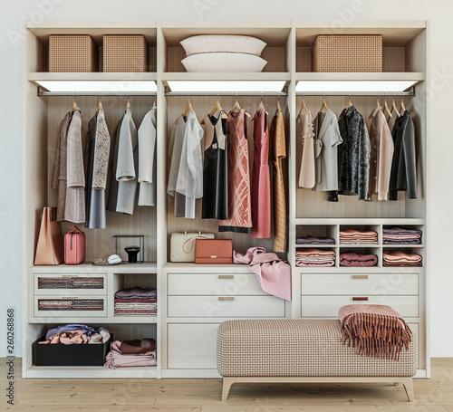 Fotografía  modern wooden wardrobe with women clothes hanging on rail in walk in closet desi