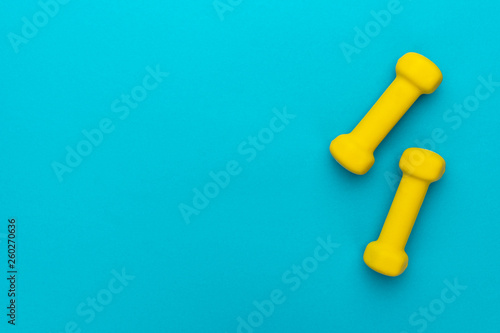 Fotografia  flat lay photo of yellow fitness dumbells over blue backgound with copy space