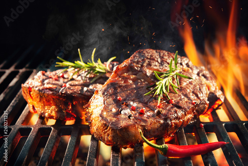 Tuinposter Vuur Beef steaks sizzling on the grill
