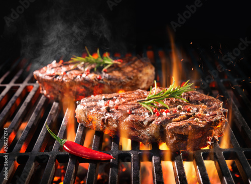 Beef steaks sizzling on the grill