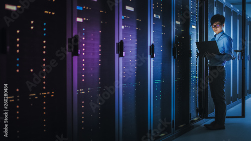 Stampa su Tela In Dark Data Center: Male IT Specialist Stands Beside the Row of Operational Server Racks, Uses Laptop for Maintenance