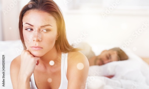 Fotografie, Tablou Dissatisfied beautiful young woman in bed with sad expression on her face, sex problems in long relationship or marriage while man sleeping