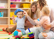 Mothers with kids play in playroom