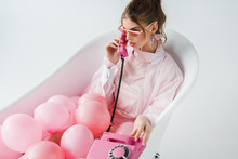 Attractive Girl In Sunglasses Talking On Retro Phone While Lying In Bathtub With Pink Air Balloons On White