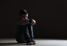 Upset Boy Sitting In Dark Room. Space For Text