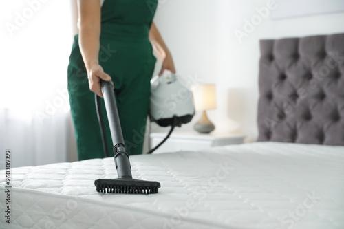 Fotografija Janitor cleaning mattress with professional equipment in bedroom, closeup