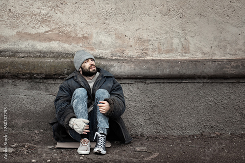 Photo Poor homeless man sitting near wall on street. Space for text