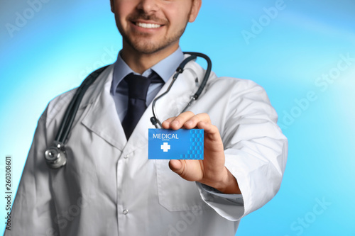 Doctor Holding Business Card On Color Background Closeup