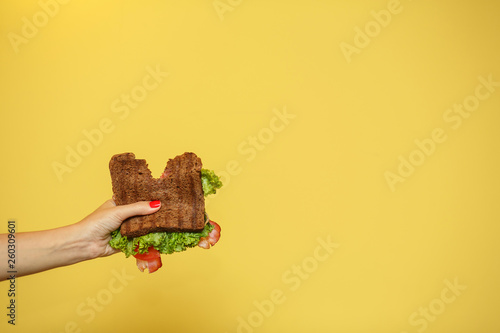 woman hands hold bitten sandwich on yellow background. Sandwich promotion concept