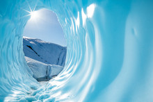 Sun Shining Into The Entrance Of A Large Round Ice Cave In The Matanuska Glacier In Alaska.