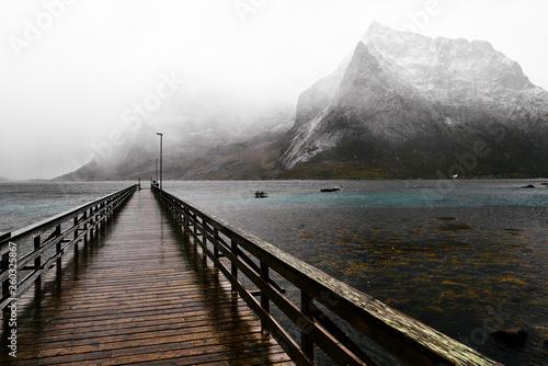 Drewniany most na Oceanie Arktycznym w Vinstad prowadzące na odległość w zimny dzień w zimie. W tle widać pokryte śniegiem góry.