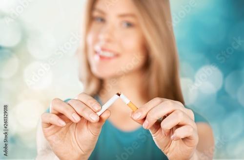 Fotografia Young woman breaking cigarette  on background
