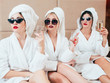 Best friends relaxation and leisure time. Beauty self assurance. Young females in bathrobes and champagne sitting on bed.