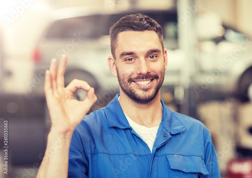 Fototapeta car service, repair, maintenance and people concept - happy smiling auto mechanic man or smith showing ok hand sign at workshop obraz