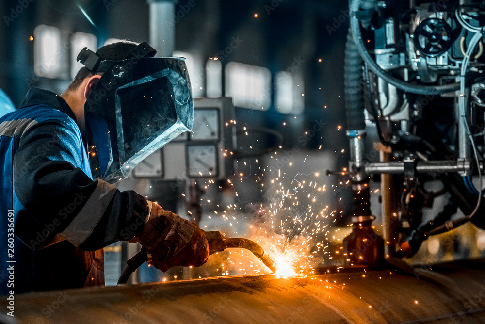 Fototapety, obrazy: man welds at the factory
