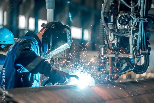 Obraz na plátně  man welds at the factory