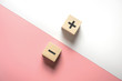 The concept of opposites, wood blog with plus and minus  on white and pink background, flat lay, copy space, top view.