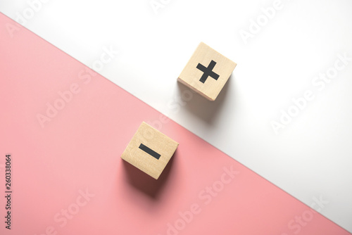 Fotografie, Obraz  The concept of opposites, wood blog with plus and minus  on white and pink background, flat lay, copy space, top view