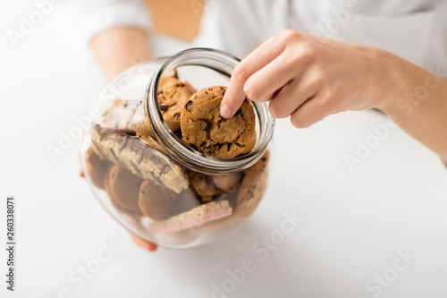 Fotografiet food, pastry and eating concept - close up of woman taking oatmeal cookies from