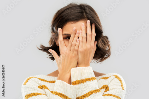 Obraz people concept - happy smiling young woman in striped pullover closing face with hands and looking by one eye through her fingers over grey background - fototapety do salonu