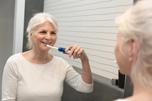 Electric Toothbrush Used By Senior Woman