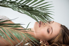 Attractive Young Woman Lying Near Tropical Palm Leaves With Closed Eyes On White