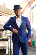 cool african american male model posing on city street with suit and bowtie