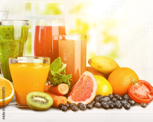 Photo Stands Juice Tasty fruits and juice with vitamins on background