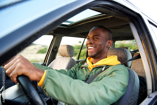 Side of happy african american man driving car Fototapet