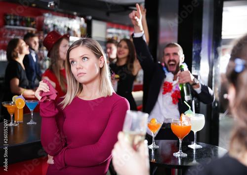 Fototapeta Girl upset with drunk boyfriend on Hawaiian party in bar